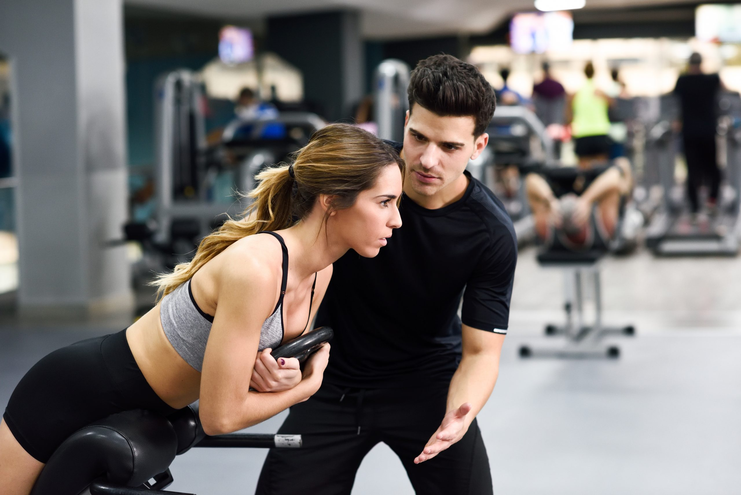 Personal trainer helping young woman lift weights